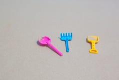 Ζωηρόχρωμο παιχνίδι παιδιών, δίκρανο κουταλιών στην παραλία άμμου Στοκ φωτογραφία με δικαίωμα ελεύθερης χρήσης