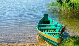 Ζωηρόχρωμο πράσινο αλιευτικό σκάφος με τα κουπιά στοκ εικόνες