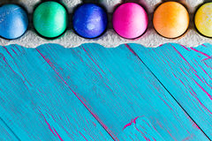 Ζωηρόχρωμο πλαίσιο αυγών Πάσχας στο εξωτικό μπλε copyspace Στοκ Φωτογραφίες