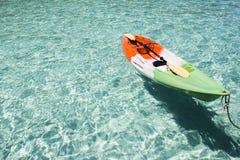 Ζωηρόχρωμο πλαστικό κανό στην αμμώδη παραλία νερού στοκ φωτογραφία