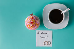 Ζωηρόχρωμο ρόδινο cupcake στο υπόβαθρο aquamarine με το φλυτζάνι καφέ Στοκ Εικόνα