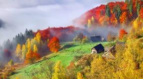 Ζωηρόχρωμο τοπίο φθινοπώρου στο ορεινό χωριό ομιχλώδες πρωί Στοκ Εικόνες