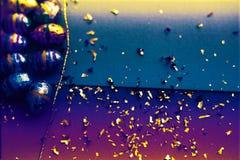 Ζωηρόχρωμο υπόβαθρο Πάσχας Χρυσό κομφετί στα χρωματισμένα φύλλα Χρυσό αυγό Πάσχας στην επιφάνεια Τοπ άποψη των ρυθμίσεων ντεκόρ στοκ φωτογραφία