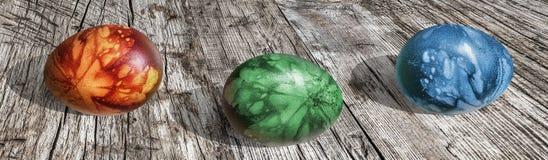 Ζωηρόχρωμο χέρι αυγών Πάσχας που χρωματίζεται και που διακοσμείται με τις σφραγίδες φύλλων ζιζανίων που τίθενται στον παλαιό ραγι Στοκ Φωτογραφίες