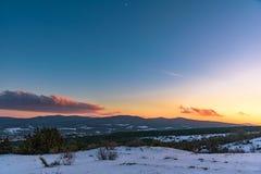 Ζωηρόχρωμο χειμερινό ηλιοβασίλεμα στο υπόβαθρο βουνών με έναν θεαματικό ουρανό Ρωσία, Stary Krym Στοκ Φωτογραφία