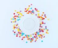 Ζωηρόχρωμο ψέκασμα βιομηχανιών ζαχαρωδών προϊόντων των αστεριών και άσπρο δαντελλωτός doily εγγράφου σε ένα ελαφρύ υπόβαθρο Στοκ Φωτογραφία