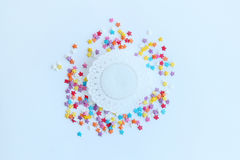 Ζωηρόχρωμο ψέκασμα βιομηχανιών ζαχαρωδών προϊόντων των αστεριών και άσπρο δαντελλωτός doily εγγράφου σε ένα ελαφρύ υπόβαθρο στοκ φωτογραφίες