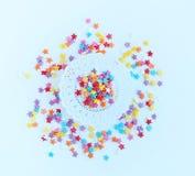 Ζωηρόχρωμο ψέκασμα βιομηχανιών ζαχαρωδών προϊόντων των αστεριών και άσπρο δαντελλωτός doily εγγράφου σε ένα ελαφρύ υπόβαθρο στοκ εικόνες