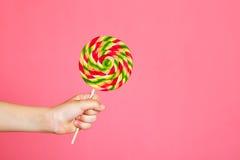 Ζωηρόχρωμο lollipop στο χέρι παιδιών στο ρόδινο υπόβαθρο Στοκ εικόνες με δικαίωμα ελεύθερης χρήσης