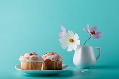 Ζωηρόχρωμο muffin στο πιατάκι με το λουλούδι Υπόβαθρο χρώματος Aqua Στοκ Φωτογραφίες