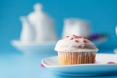 Ζωηρόχρωμο muffin στο πιατάκι με το πέταλο λουλουδιών Στοκ Εικόνα