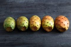 Ζωηρόχρωμο opuntia ή τραχιών αχλαδιών φρούτα στο υπόβαθρο πετρών Στοκ Εικόνες