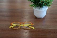 Ζωηρόχρωμο orage και κίτρινα γυαλιά και άσπρο δοχείο λουλουδιών σε ξύλινο Στοκ Φωτογραφία