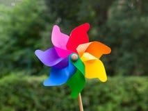 Ζωηρόχρωμο pinwheel στα δέντρα κήπων που θολώνονται στο υπόβαθρο Στοκ Εικόνες