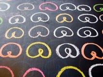 Ζωηρόχρωμο pretzel που επισύρει την προσοχή σε έναν πίνακα κιμωλίας Στοκ Φωτογραφίες