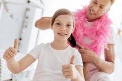 Ζωηρό ενθουσιώδες κορίτσι που παίρνει την τρίχα της γίνοντη από τον πατέρα Στοκ Εικόνες