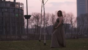 Ζωηρό ροδανιλίνης ηλιοβασίλεμα - η νέα έγκυος γυναίκα είναι ευτυχής στη χώρα προορισμού ταξιδιού της Λετονία με μια άποψη πέρα απ φιλμ μικρού μήκους