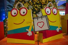 Ζωντανεψοντες Smiley τσάντες αγορών με το χριστουγεννιάτικο δέντρο στο υπόβαθρο στοκ φωτογραφία