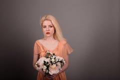 Ζωντανό κορίτσι κουκλών με τα λουλούδια σε ένα γκρίζο υπόβαθρο Στοκ Φωτογραφίες