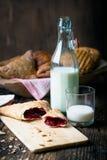 ζύμες προγευμάτων με τη μαρμελάδα και το γάλα στοκ φωτογραφίες