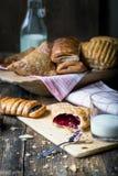 ζύμες προγευμάτων με τη μαρμελάδα και το γάλα στοκ εικόνες