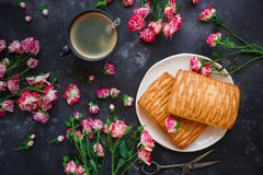 Ζύμες ριπών και καφές, γλυκά και λουλούδια, σκοτεινό υπόβαθρο, τοπ άποψη, στις 8 Μαρτίου, ημέρα των γυναικών στοκ εικόνα