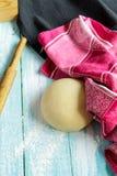 Ζύμη, κυλώντας καρφίτσα και ρόδινη πετσέτα στους ανοικτό μπλε πίνακες Στοκ Φωτογραφίες