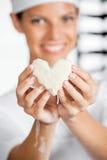 Ζύμη μορφής καρδιών εκμετάλλευσης Baker στο αρτοποιείο Στοκ εικόνα με δικαίωμα ελεύθερης χρήσης