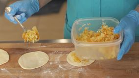 Ζύμη πλήρωσης αρτοποιών αρχιμαγείρων πρίν ψήνει patties στον ξύλινο πίνακα στο κατάστημα κέικ απόθεμα βίντεο