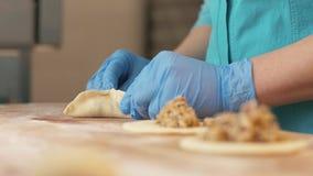 Ζύμη πλήρωσης χεριών Baker και διαμόρφωση patty στον πίνακα στην κινηματογράφηση σε πρώτο πλάνο καταστημάτων αρτοποιείων φιλμ μικρού μήκους
