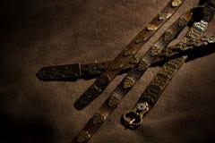 Ζώνες δέρματος με τη διακόσμηση του μετάλλου που απομονώνεται στο σκοτεινό backgrou Στοκ Φωτογραφίες