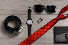 Ζώνη δέρματος, ρολόι, γυαλιά ηλίου, κόκκινος δεσμός μεταξιού, μανικετόκουμπα, notebo Στοκ Φωτογραφίες