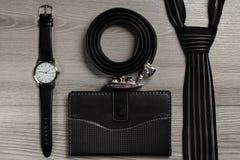 Ζώνη δέρματος Dlack, ρολόι, δεσμός μεταξιού, σημειωματάριο σε ένα γκρίζο backgrou Στοκ Εικόνες