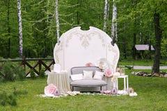 Ζώνη φωτογραφιών με τα ονόματα και τον καναπέ newlyweds, με το ντεκόρ λουλουδιών Στοκ Εικόνα