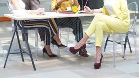Ηγέτης στο κίτρινο καθιερώνον τη μόδα κοστούμι ελέγχοντας εργασία των συναδέλφων της απόθεμα βίντεο