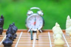 Ηγεσία για το παιχνίδι επιτυχίας, το μικροσκοπικό επιχειρηματία που στέκονται στο υπόβαθρο σκακιερών και σκακιού, την επένδυση στ στοκ φωτογραφία με δικαίωμα ελεύθερης χρήσης