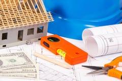 Ηλεκτρικά διαγράμματα, εργαλεία και εξαρτήματα εργασίας, σπίτι κάτω από την κατασκευή και δολάριο νομισμάτων Στοκ Εικόνα
