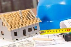 Ηλεκτρικά σχέδια, εργαλεία εργασίας και εξαρτήματα για τις εργασίες μηχανικών, μικρά σπίτι και δολάριο νομισμάτων, έννοια εγχώριω Στοκ Φωτογραφίες