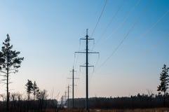 Ηλεκτρικές γραμμές μετάδοσης το χειμώνα, χιονισμένοι τομείς το βράδυ στοκ εικόνα