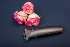 Ηλεκτρική γραφομηχανή ατόμων ` s, trimmer, για την τέμνουσα τρίχα σε ένα μπλε υπόβαθρο με τα τριαντάφυλλα στοκ φωτογραφία με δικαίωμα ελεύθερης χρήσης