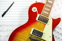 Ηλεκτρική κιθάρα με τις σημειώσεις μουσικής στο υπόβαθρο Στοκ φωτογραφία με δικαίωμα ελεύθερης χρήσης