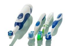 Ηλεκτρική οδοντόβουρτσα και τρεις χειρωνακτικές βούρτσες στα διαφορετικά χρώματα, που απομονώνονται στο λευκό Στοκ φωτογραφία με δικαίωμα ελεύθερης χρήσης