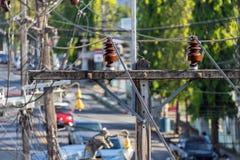 Ηλεκτρικοί μονωτές και καλώδια στους πόλους στην Ασία στοκ εικόνες