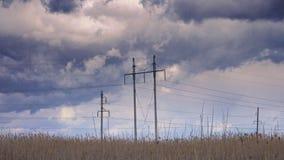 Ηλεκτρικοί πυλώνες ενάντια στον ουρανό με τα thunderclouds απόθεμα βίντεο