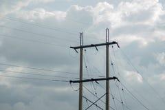 Ηλεκτρικοί πόλοι εκτός από το κύριο δρόμο σε νεφελώδη στοκ εικόνες
