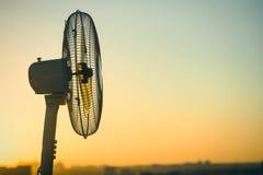 Ηλεκτρικός εξαεριστήρας ανεμιστήρων σε ένα κλίμα ενός σαφούς ουρανού ηλιοβασιλέματος Έννοια στοκ φωτογραφία