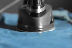 Ηλεκτρικός σίδηρος σε ένα ζευγάρι των τζιν τζιν Στοκ Φωτογραφίες