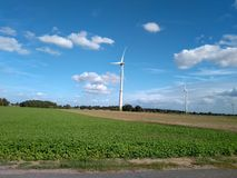 Ηλεκτρικός στρόβιλος ανεμόμυλων πέρα από τους γερμανικούς πράσινους τομείς γεωργίας στοκ φωτογραφία με δικαίωμα ελεύθερης χρήσης