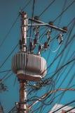 Ηλεκτρικός υψηλής τάσεως πόλος δύναμης με τη μονάδα μετασχηματιστών Στοκ Φωτογραφία