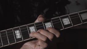 ηλεκτρικό απομονωμένο χέρι άτομο κιθαριστών κιθάρων που παίζει το λευκό έξι συμβολοσειράς Αρσενικά χέρια με την ηλεκτρική κιθάρα φιλμ μικρού μήκους